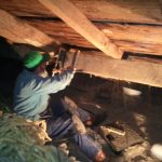 Timber framer, Scott Galliford, repairs a cracked purlin in the Stone Store attic.