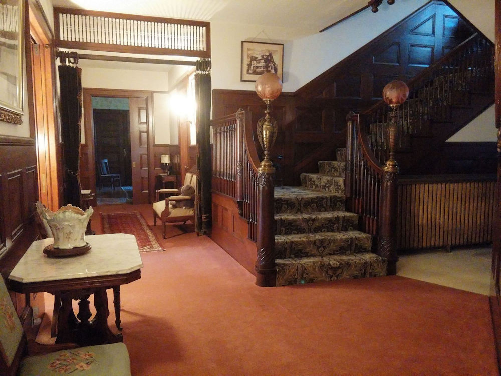Entry hall and staircase of the house at 12-14 Church Street in LeRoy, NY.